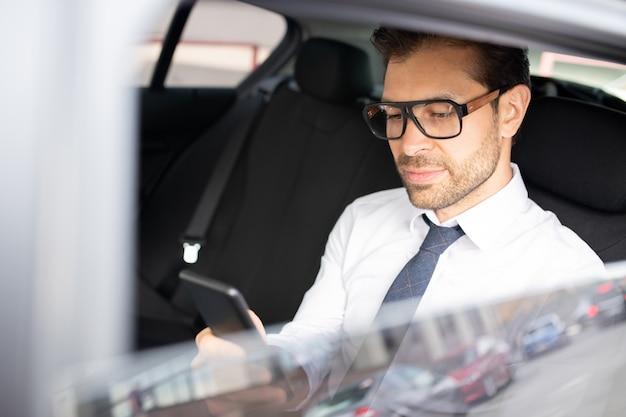 Beschäftigter eleganter junger mann mit smartphone, das im auto sitzt und am morgen sms oder kontakt sucht