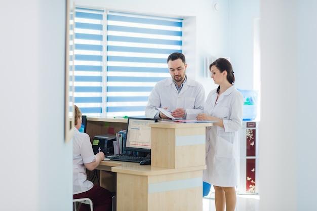 Beschäftigter empfang in einem krankenhaus mit ärzten und rezeptionisten