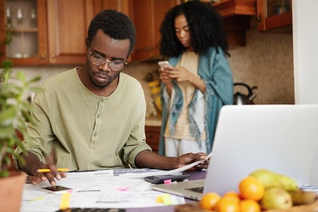 Beschäftigter ernsthafter afrikanischer mann, der handy benutzt, während familienausgaben berechnet und papierkram erledigt