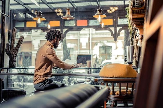 Beschäftigter freiberufler. ernsthafte männliche person, die in halber position sitzt, während sie an seinem projekt arbeitet