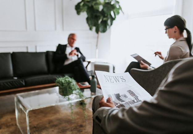 Beschäftigter geschäftsmann, der in der lounge eine zeitung liest