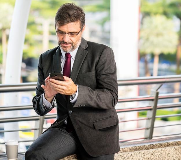 Beschäftigter geschäftsmann, der sein telefon überprüft