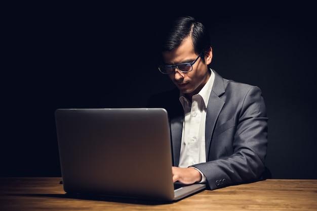 Beschäftigter geschäftsmann, der spät im büro nachts arbeitet