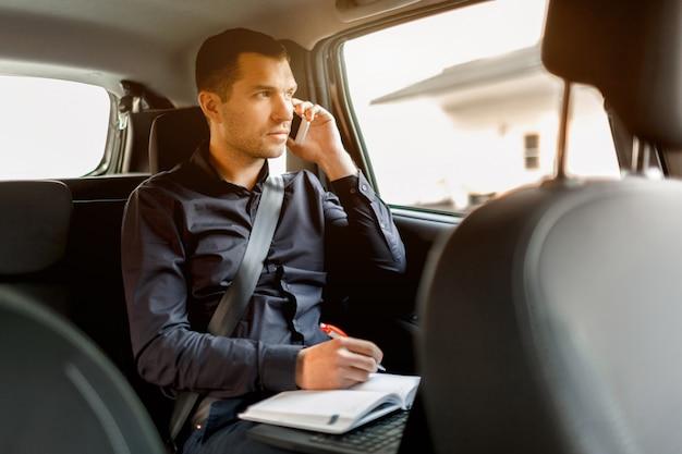 Beschäftigter geschäftsmann in einem taxi. multitasking-konzept. der passagier fährt auf dem rücksitz und arbeitet gleichzeitig. spricht auf einem smartphone und schreibt auf ein notebook.