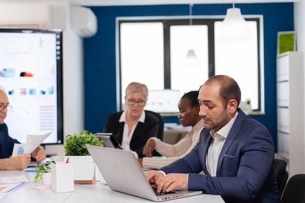 Beschäftigter geschäftsmann mit laptop, der am konferenztisch im broadroom sitzt und sich auf die arbeit konzentriert