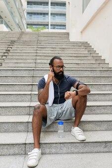 Beschäftigter indischer läufer mit brille, der auf treppen sitzt und nach dem trainingstraining audionachrichten in kopfhörern hört