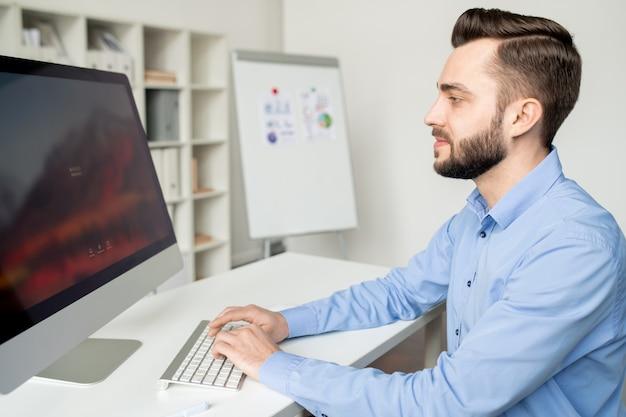 Beschäftigter junger analytiker, der am schreibtisch vor dem computerbildschirm sitzt, während er tippt und nach informationen oder websites sucht