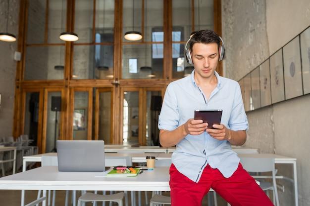 Beschäftigter junger attraktiver lächelnder glücklicher mann, der tablett verwendet, das musik auf drahtlosen kopfhörern hört,