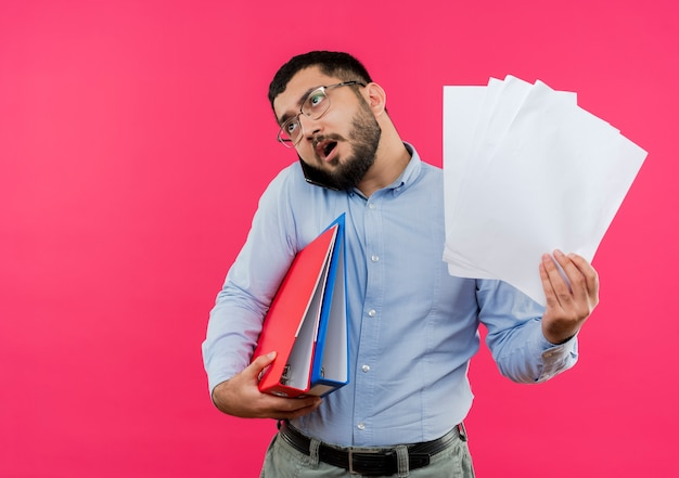 Beschäftigter junger bärtiger mann in den gläsern und im blauen hemd, die ordner und leere seiten halten, während auf handy sprechen