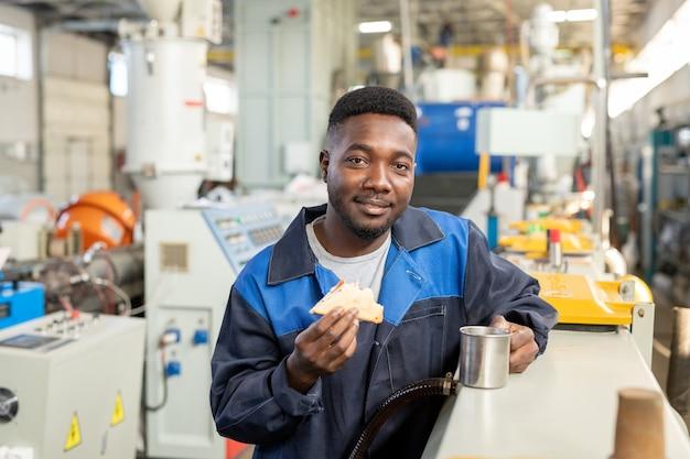 Beschäftigter junger fabrikarbeiter in overalls, der die arbeitsdatei auf dem tablet überprüft, während er in der industrie arbeitet