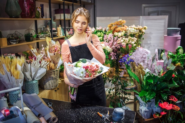Beschäftigter junger florist halten blumenstrauß in der hand. sie telefoniert. junge frau stehen im raum voller blumen und pflanzen.