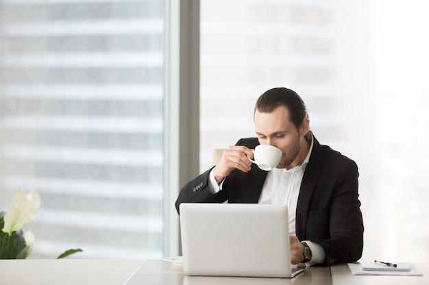 Beschäftigter junger geschäftsmann trinkt kaffee