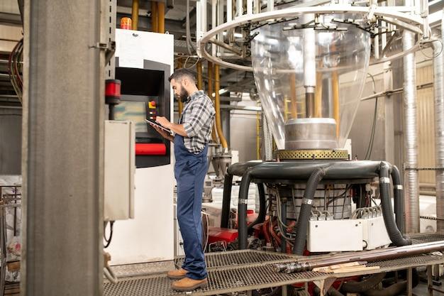 Beschäftigter junger ingenieur der polymerproduktionsfabrik, der durch bedienfeld steht, während technische daten in tablette durchgesehen werden