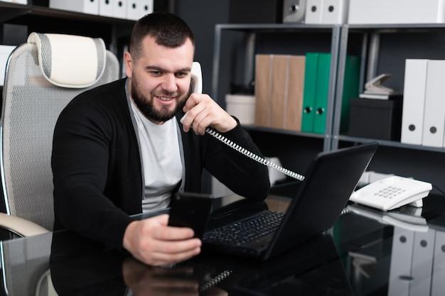 Beschäftigter junger mann, der am telefon spricht und laptop im büro betrachtet