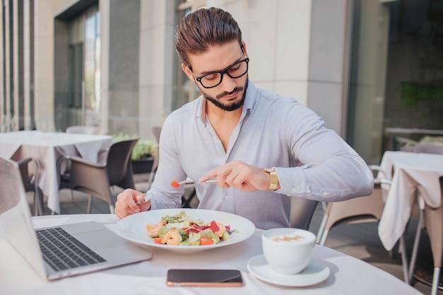 Beschäftigter junger mann sitzt am tisch vor dem restaurant. er schaut auf uhren. es gibt einen laptop, eine schüssel salat, ein telefon und eine tasse kaffee am tisch.