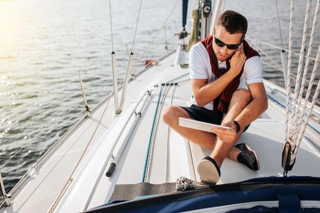 Beschäftigter junger mann sitzt an bord der yacht und telefoniert. auch er hält und schaut auf tablette. junger mann sitzt mit gekreuzten beinen. er trägt eine sonnenbrille.
