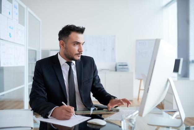 Beschäftigter kaukasischer mann in der klage, die im büro sitzt und an computer arbeitet
