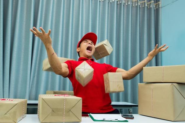 Beschäftigter kurier im büro und viele pakete in der luft.