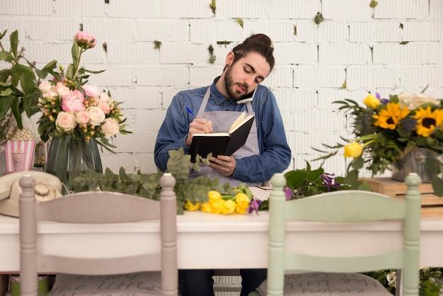 Beschäftigter männlicher florist, der bestellung am handy entgegennimmt und es auf notizbuch notiert