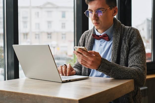 Beschäftigter männlicher manager, der am handy spricht und auf armbanduhr beim sitzen am laptop im café betrachtet