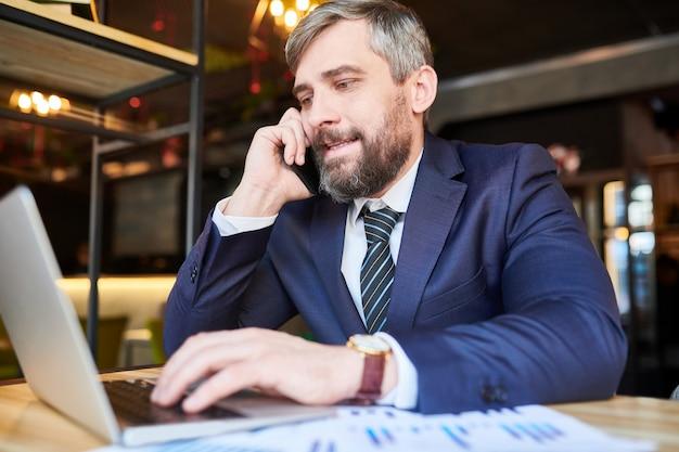 Beschäftigter makler in abendgarderobe, der jemanden am telefon konsultiert, während er durch die online-informationen im laptop blättert