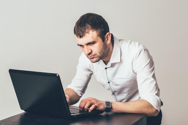 Beschäftigter mann arbeitet an dem laptop im büro. der geschäftsmann konzentriert sich auf die lösung der aufgaben