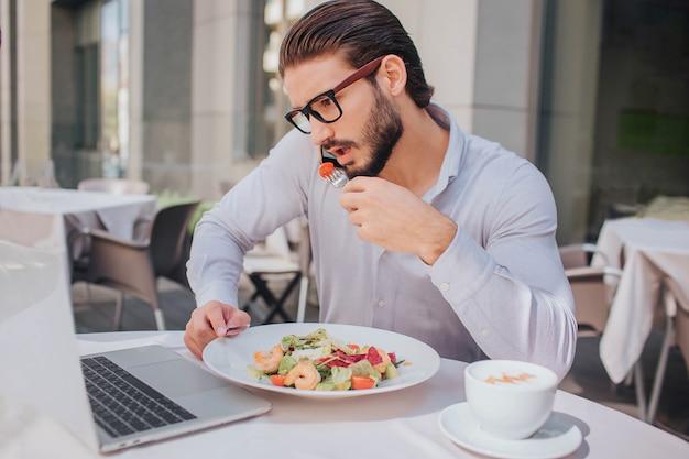 Beschäftigter mann beantwortet anruf während des mittagessens. er redet und hält gleichzeitig teller mit salat. es gibt auch eine tasse kaffee.