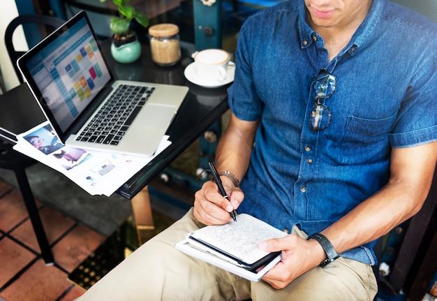 Beschäftigter mann, der an einem laptop arbeitet