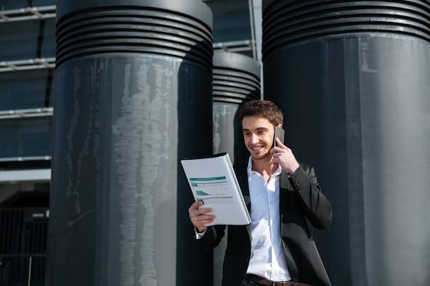 Beschäftigter mann, der dokumente hält und am telefon spricht