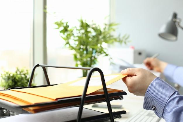 Beschäftigter mann, der mit dokumenten im büro arbeitet