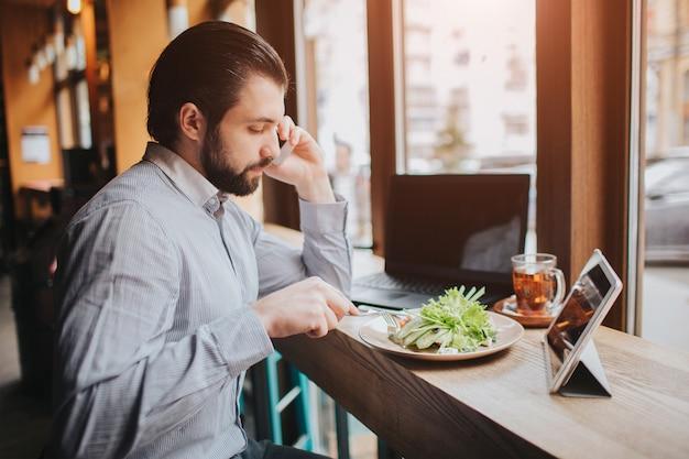 Beschäftigter mann hat es eilig, er hat keine zeit. arbeiter essen, kaffee trinken, gleichzeitig telefonieren. geschäftsmann, der mehrere aufgaben erledigt. multitasking-unternehmer.