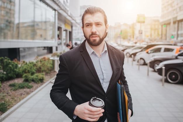 Beschäftigter mann hat es eilig, er hat keine zeit, er wird unterwegs telefonieren. geschäftsmann, der mehrfache aufgaben auf der haube des autos erledigt. multitasking-geschäftsmann trinkt kaffee