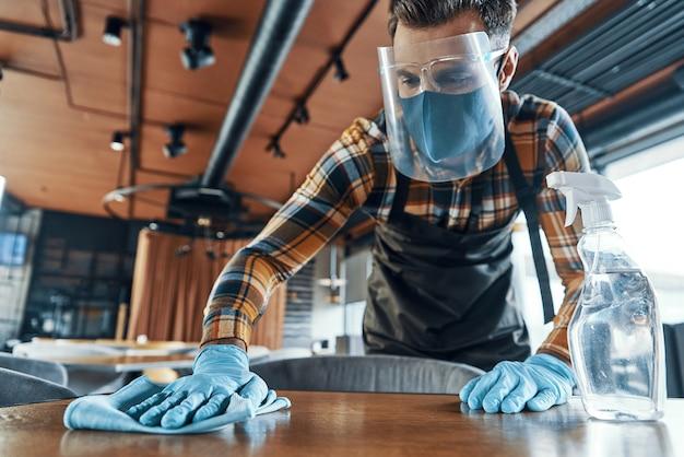 Beschäftigter mann im reinigungstisch des schützenden gesichtsschutzes im restaurant