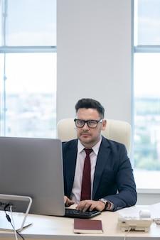 Beschäftigter mann in abendgarderobe, der auf der computertastatur tippt