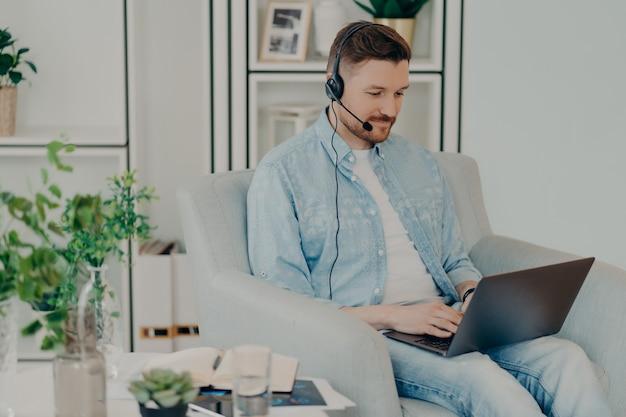 Beschäftigter mann in jeanskleidung liefert beraterservice-typen auf laptop-computer trägt kopfhörer mit mikrofon arbeitet entfernt sitzt in bequemen sesseln nimmt an online-verhandlungen teil