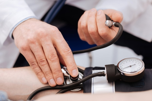 Beschäftigter prominenter privatarzt, der einen test an seinem patienten mit speziellen geräten zur messung seines blutdrucks durchführt