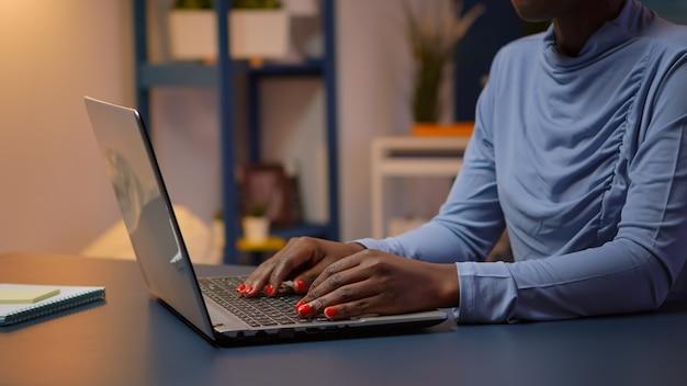 Beschäftigter schwarzer angestellter, der spät nachts auf dem computer sitzt, der im modernen wohnzimmerbüro auf einem stuhl sitzt. afrikanischer unternehmer, der am persönlichen arbeitsplatz auf der tastatur mit blick auf den desktop schreibt