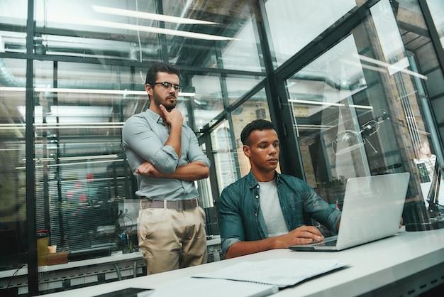 Beschäftigter tag zwei junge und gutaussehende männer in freizeitkleidung, die auf den bildschirm des laptops schauen