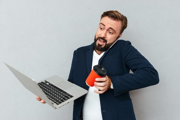 Beschäftigter überraschter bärtiger mann in geschäftskleidung, die durch smartphone spricht