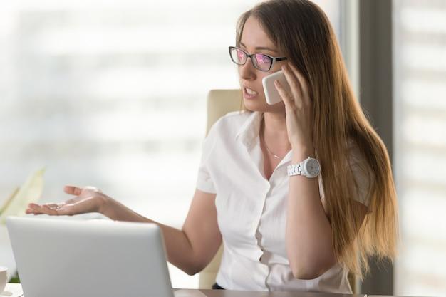 Beschäftigter weiblicher unternehmer, der telefonisch argumentiert