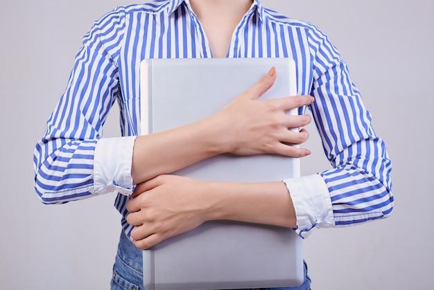 Beschäftigter weiblicher verwalter in einem gestreiften weiß-blauen hemd mit gläsern und einem laptop. mitarbeiterin des jahres, business lady.