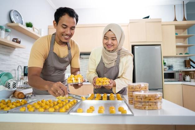 Beschäftigtes paar, das zu hause zusammen nastar-snack-kuchen für die gemeinsame eid mubarak-feier macht