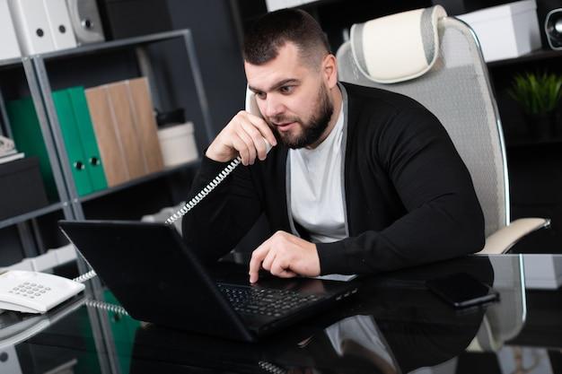 Beschäftigtes unterhaltungstelefon des jungen mannes und betrachten des laptops im büro
