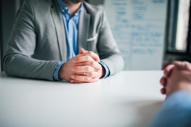 Beschäftigungs- und rekrutierungskonzept. zwei geschäftsleute, die vor einander im büro sitzen und, nahaufnahme sich besprechen.