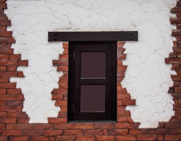 Beschaffenheit des dunkelbraunen fensterrahmens auf dem zement und der backsteinmauer eines hauses