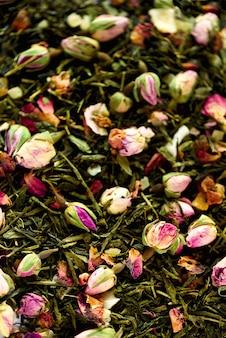 Beschaffenheit des grünen tees mit den rosafarbenen blumenblättern. getrocknete rosebuds-beschaffenheitsnahaufnahme. essen. bio gesunde kräuterblätter, detox tee.