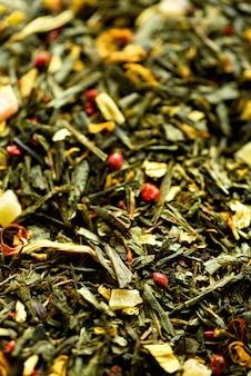 Beschaffenheit des grünen tees mit gelben blumen der getrockneten blumenblätter und rotem pfeffer. essen. bio gesunde kräuterblätter, detox tee.
