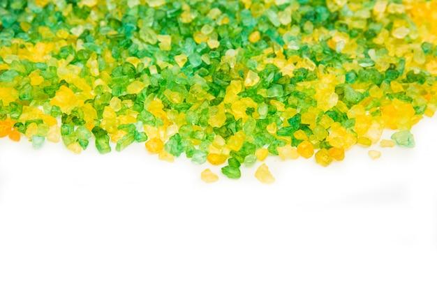Beschaffenheit des grünen und gelben salzes für das bad. salz auf weißem hintergrund. isoliert auf weiß