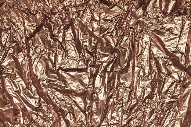 Beschaffenheit des zerknitterten blattes der bronzefolie, hintergrundnahaufnahme.