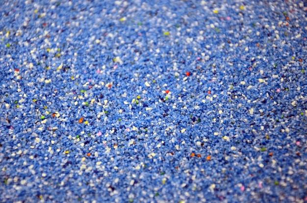 Beschaffenheit eines farbigen körnigen sandabschlusses oben. blaue körner